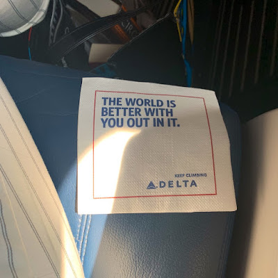 "Delta Air napkin reading, ""The world is better with you out in it."""