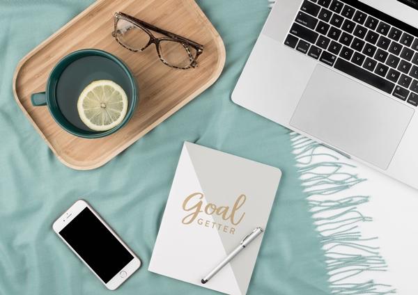 Flatlay celular, óculos, café e caderneta de metas e transformação de vida