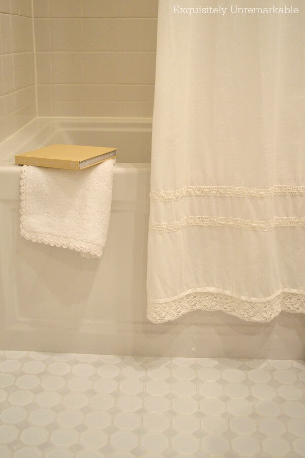 White Farmhouse Shower Curtain and crochet tipped towel draped over tub