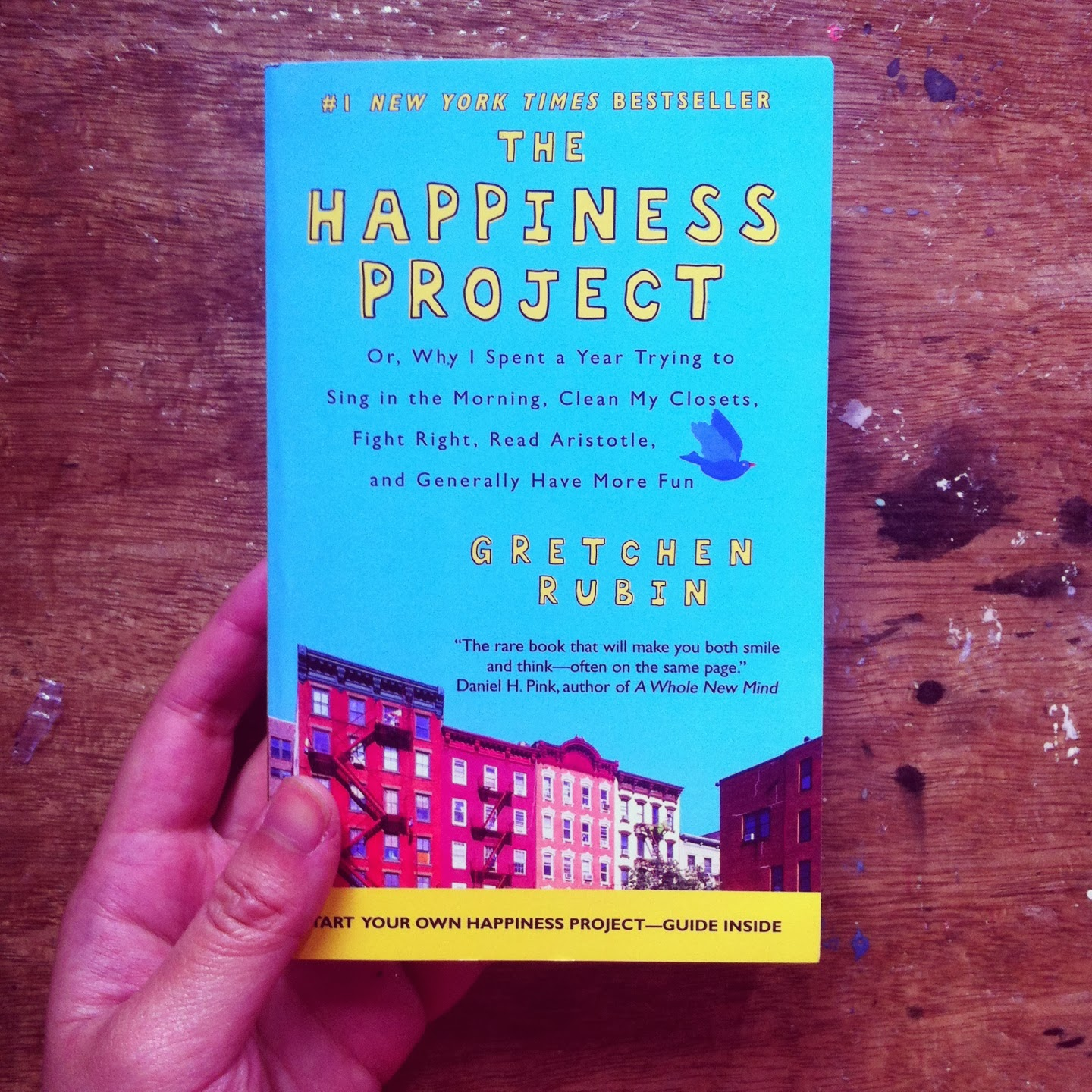 hand holding Happiness Project book on wood table