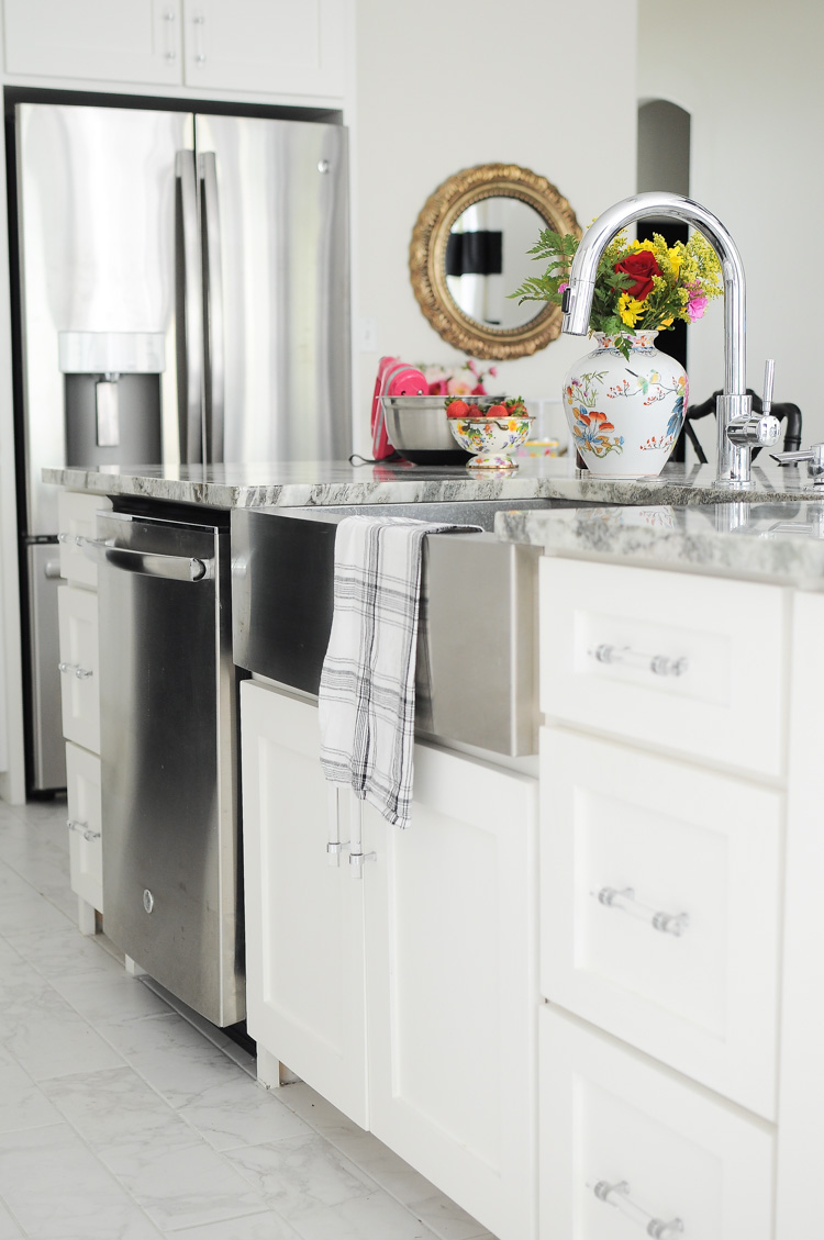 Big farmhouse sink looks modern against this all white kitchen with chrome and crystal accents.