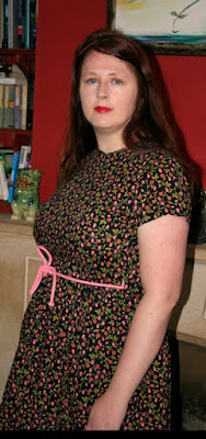 A brown-haired woman in a floral wrap dress