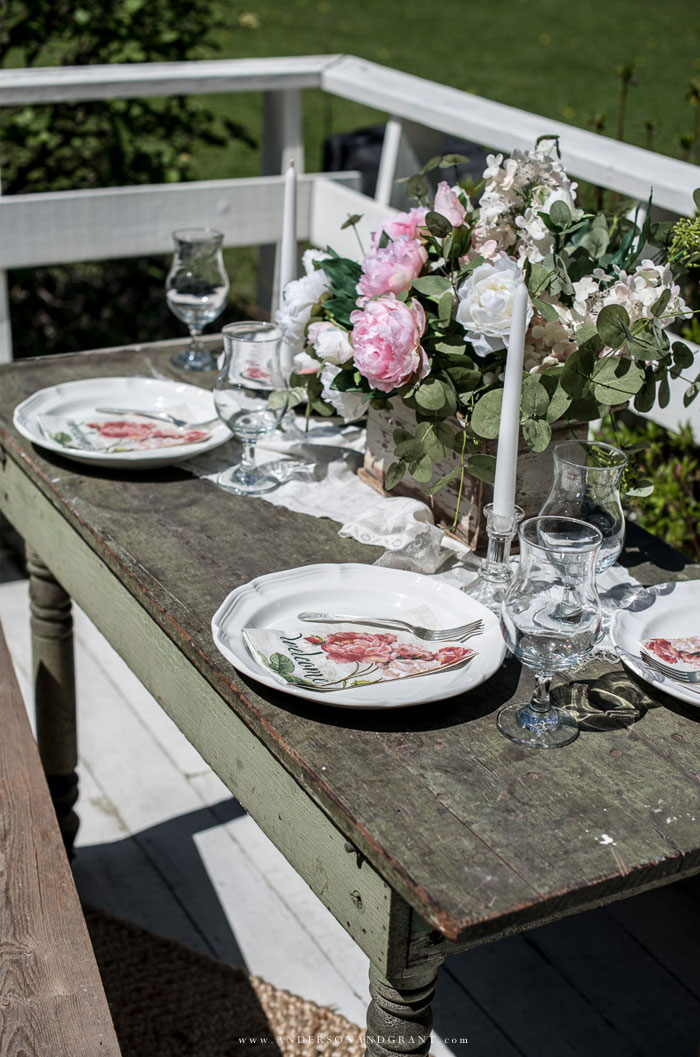 Green farmhouse table decorated outside with peony centerpiece