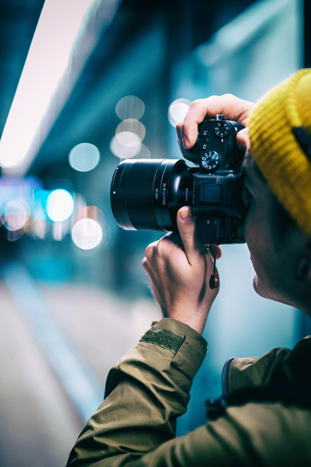 Объектив Tokina ATX-M 85mm f/1.8 FE с камерой Sony в руках фотографа