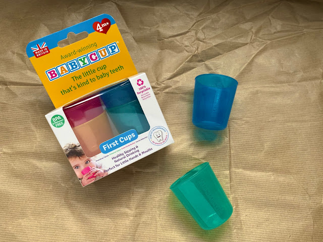 Little plastic cups in blue next to a packet containing a 4 pack of babycup first cups
