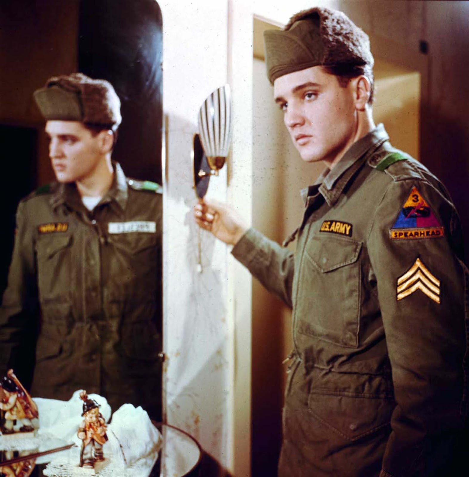 Elvis poses for a portrait next to a mirror during his tour of duty in Germany.