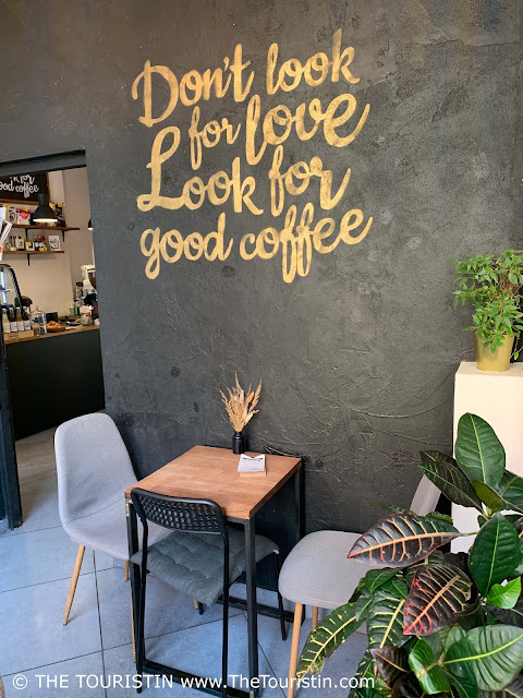 Two chairs on a delicate wooden table in front of a dark grey wall with golden letters: Don't Look for Love. Look for good coffee. Decorated with green plants. A view into the next room through a doorway.