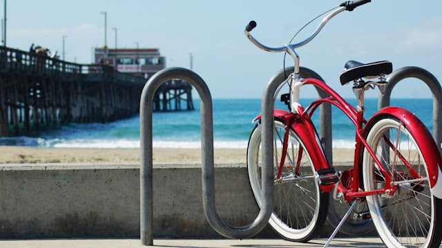 a red beach cruiser in front of the pier