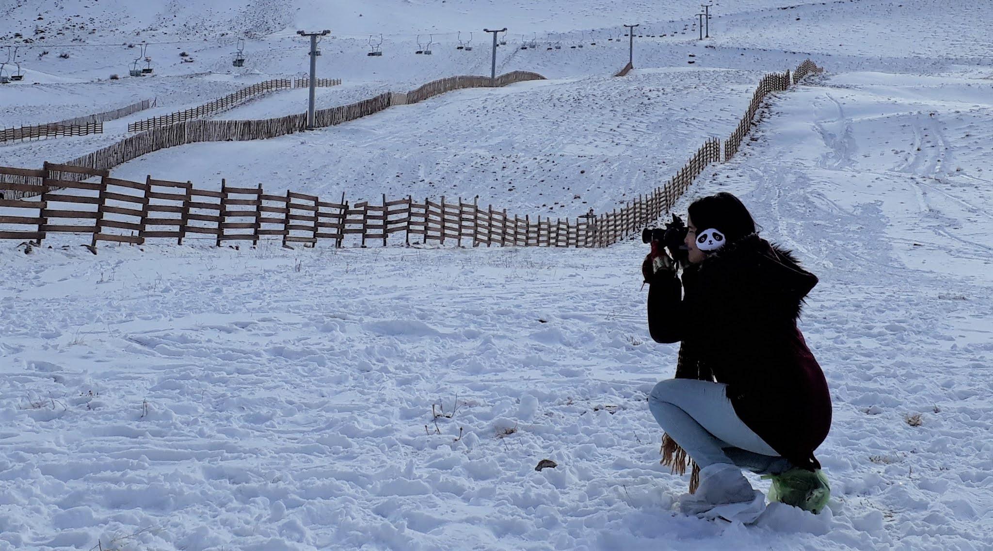 mulher fotografando paisagens na neve