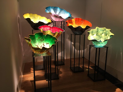 photo of 6 large glass scupltures,like giant glass poppies in bright colours