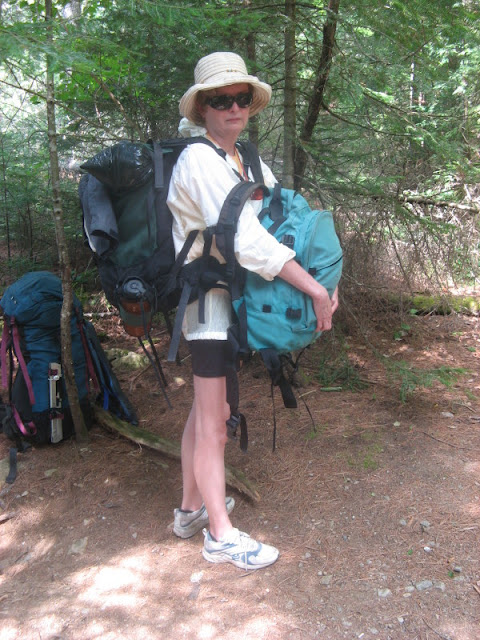 woman holding two packs in a wilderness setting