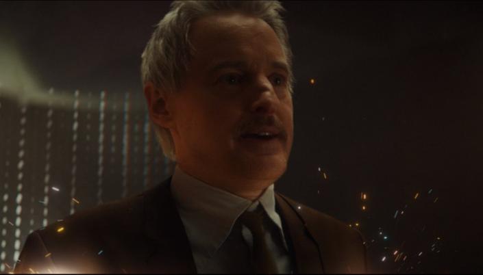 Imagem: o personagem Agente Mobius, interpretado por Owen Wilson, um homem branco com bigode escuro, cabelos loiros curtos, em um terno marrom com faíscas brancas ao seu redor, enquanto ele se desintegra.