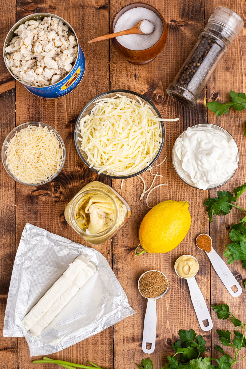 Photo of the ingredients needed to make Low Carb Artichoke Crab Dip on a wooden table.
