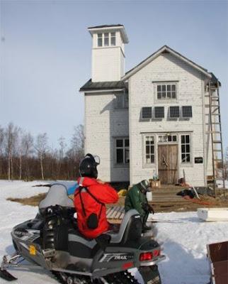 Tutkimusasema, edessä kaksi ihmistä ja moottorikelkka talvella.