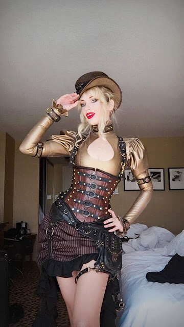 Amy Wilder dressed in women's steampunk clothing: gold bodysuit, brown corset, hat, pinstriped skirt, leather hip/thigh bag