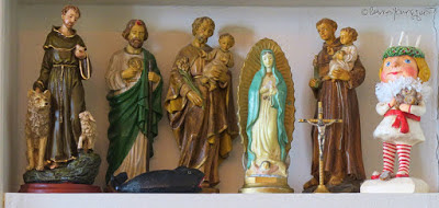 A photograph featuring statuettes on a shelf. Left to right they include, Saint Francis with animals, Saint Joseph holding Baby Jesus, Saint Jude, Our Lady of Guadeloupe, Saint Lucia, and Saint Anthony holding the Infant Jesus. These saints are featured in posts within my blog @ https://www.thelastleafgardener.com/search/label/Saints