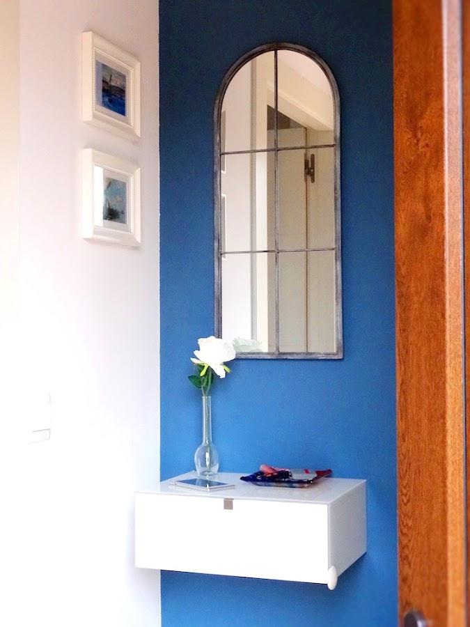 Pequeño hall con mueble volado, espejo y pared azul petróleo