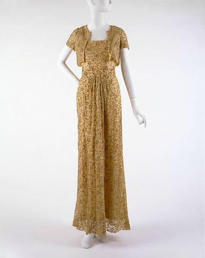 Gold beaded evening gown by Mainbocher displayed on mannequin