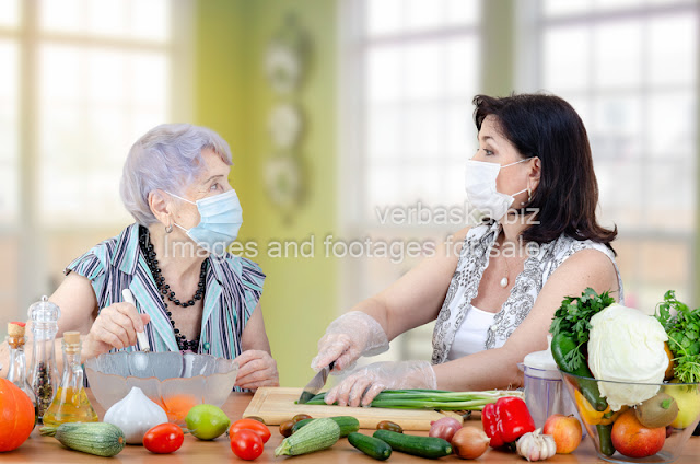 volunteer and a senior adult woman jointly make a vegetable salad
