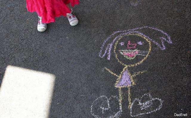 Dessin d'une fillette sur le trottoir noir