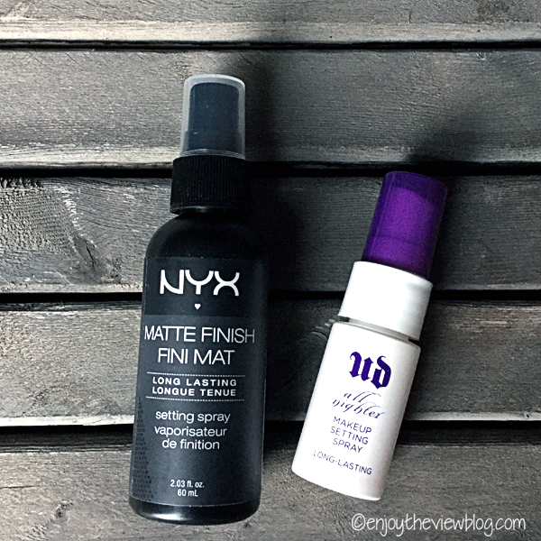 NYX Matte Finish Makeup Setting Spray and Urban Decay All Nighter Makeup Setting Spray side by side on a wooden pallet