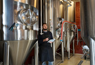 Brewmaster checks tanks in a brewery