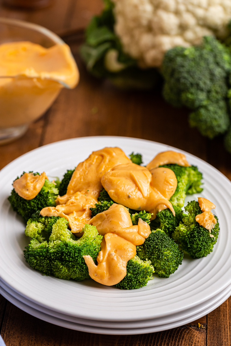 Close up photo of Easy Keto Cheese Sauce over broccoli on a white plate.