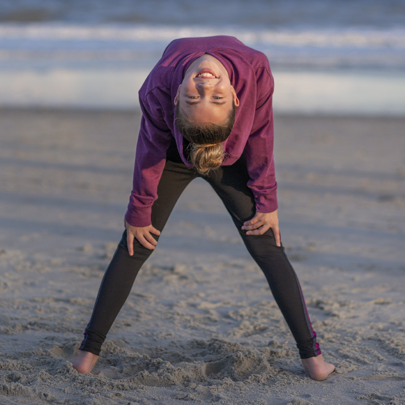 tween girl doing yoga pose on the beach contortion