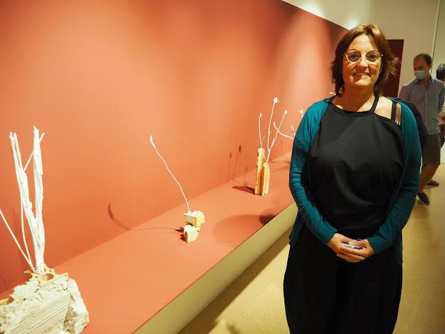 """Sama Genís, al costat d'alguna de les obres de la seva exposició """"Natures mortes""""."""