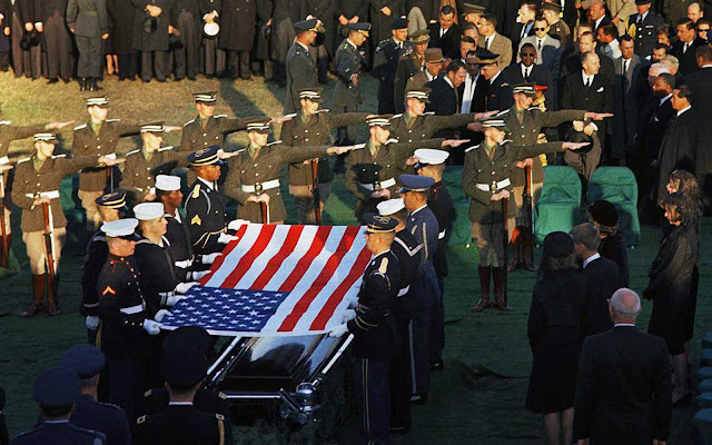 An Irish cadet honor guard, with arms outstretched, stand in formation as the U.S. flag is lifted from the coffin of President John F. Kennedy during his funeral services at Arlington National Cemetery in Arlington, Virginia, on November 25, 1963. The cadets, 18- and 19-year-old soldiers, had been whisked from their remote barracks in County Kildare the day before and were flown to the U.S. to perform a special ceremonial drill at the funeral of the slain president. He had been captivated by the drill when he saw it performed in Dublin months earlier.