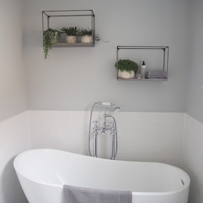Our finished bathroom renovation. Metal Farringdon Box shelves from Garden Trading with white metro tiles, a freestanding bath, freestanding taps and light grey paint