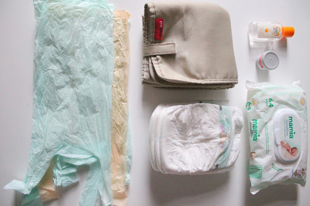 flat lay photo of contents of baby changing bag for nappy changing essential items
