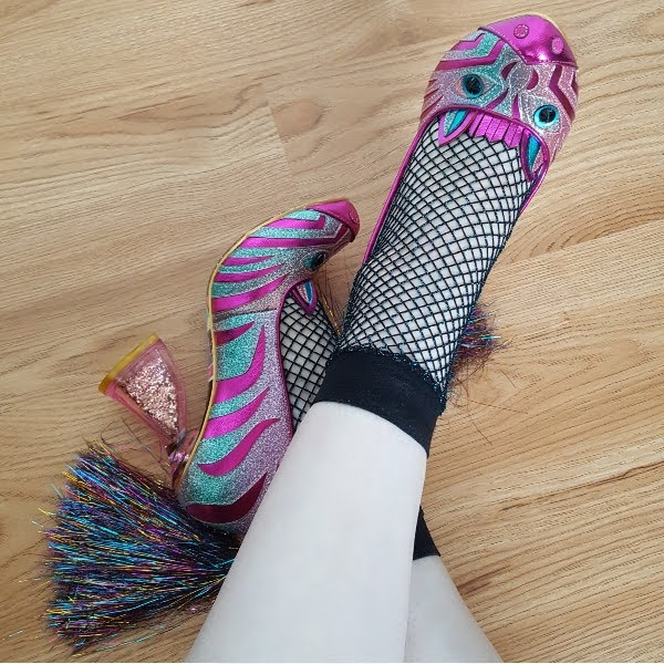 feet on wooden floor wearing bright pink zebra shoes with tinsel tail detail