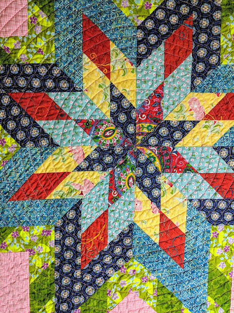 The center star of the Lone Star is machine quilted with FMQ orange peels and then switches to echo quilting in a spiral for the rest of the quilt.
