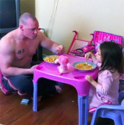 papá comiendo en la mesita rosa con su hija