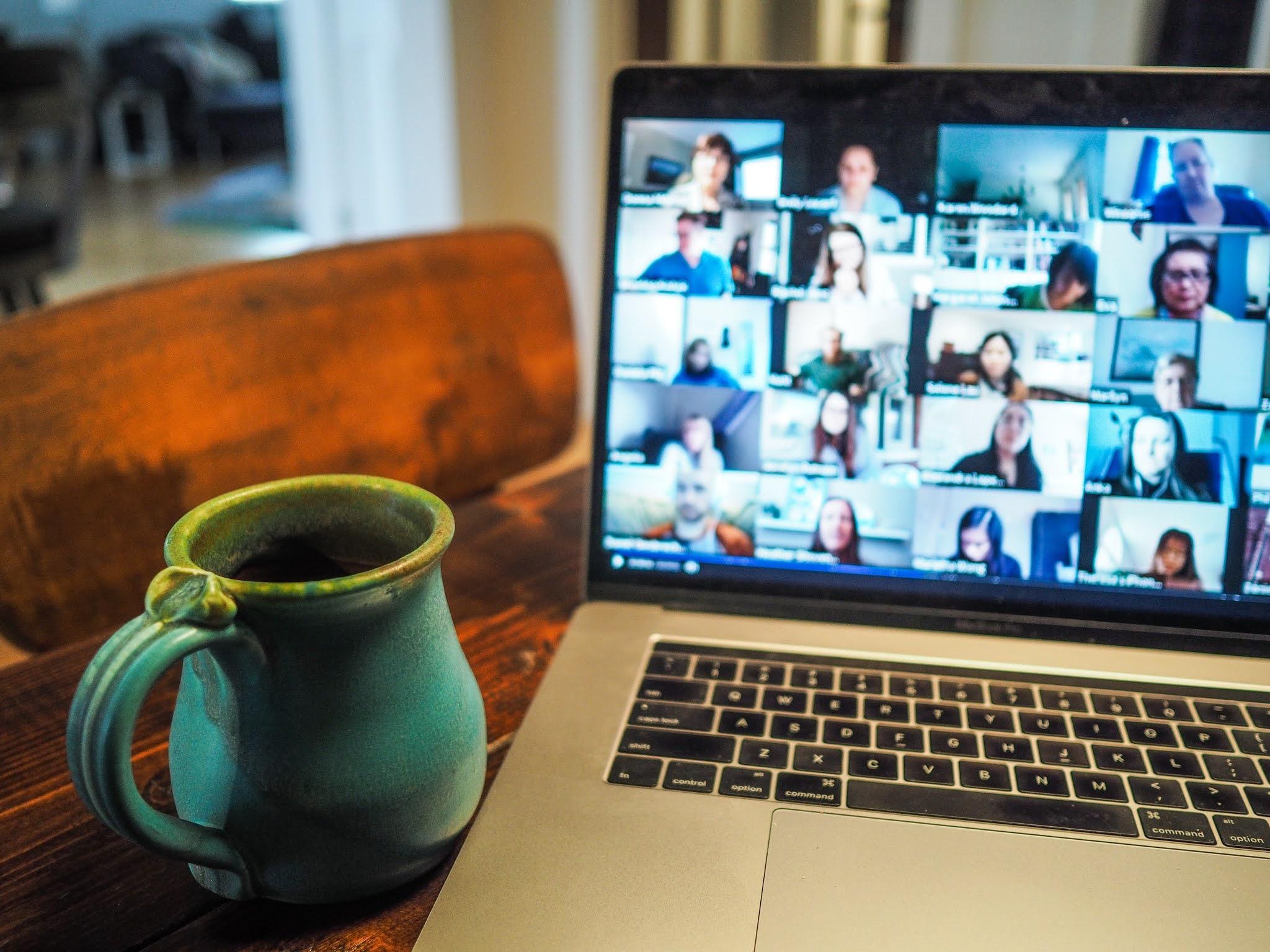 zoom quiz facetime on laptop by mug of tea