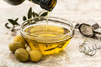 An image in which olive oil is being poured into a bowl