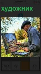 мужчина художник пишет картину на улице на мольберте