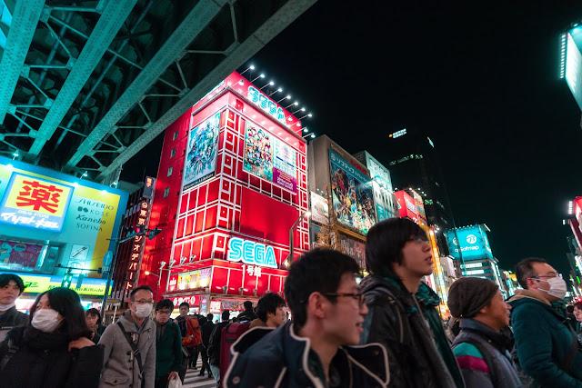Locals, tourists and otaku walking and shopping around Akihabara district near SEGA red building full of anime billboards at night.