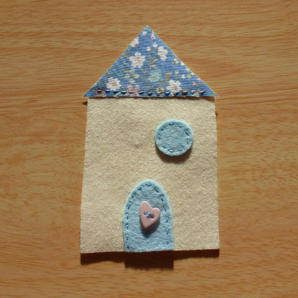 Blue and cream felt fabric house partly completed with heart button door