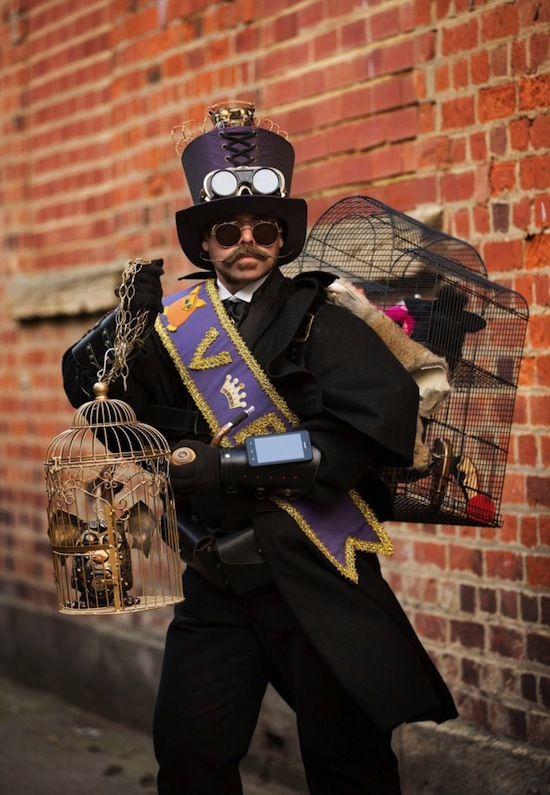 Man dressed as a Victorian ratcatcher with a steampunk twist: top hat, goggles, iphone bracer, gloves, rats in cages. Men's steampunk costumes and cosplay.