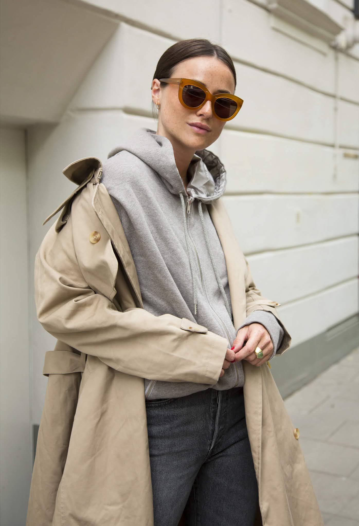 A Hoodie and Trench Coat Make for the Perfect Spring Outfit Combo —Lena Lademann in a classic trench coat, gray hooded sweatershirt, and faded black jeans
