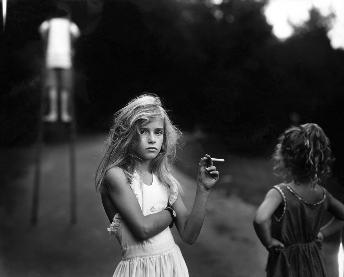 George Docking AS Photo Unit 1  Documentary Photography  Sally Mann Candy cigarette  1989 taken from the series  immediate family  is an image  of one of her family with a serious expression on her face posing with a  candy