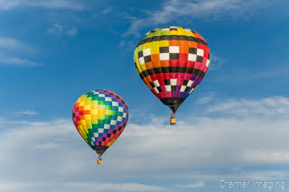 Cramer Imaging's fine art photograph of two rainbow-colored hot air balloons taking flight in Panguitch Utah with a blue partly cloudy sky