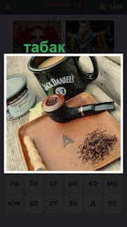 на столе на доске лежит трубка и табак с чашкой кофе