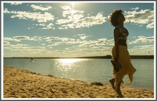 Paisagem de um grande LAGO, sol brilhante a iluminar, uma jovem pensativa, caminha descalça na areia.