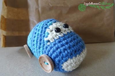 Na środku zdjęcia widnieje niebieski samochodzik wykonany z włóczki. Posiada drewniane koła z guzików. Za autem leży papierowa torba, w którą został później zapakowany.