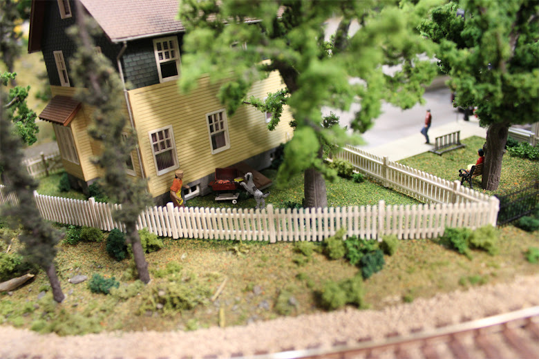 A BBQ scene and white picket fence in the back yard of a Kate's Colonial Home kit