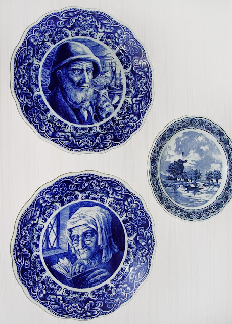 Two very large blue and white plates with an old man and and old woman.