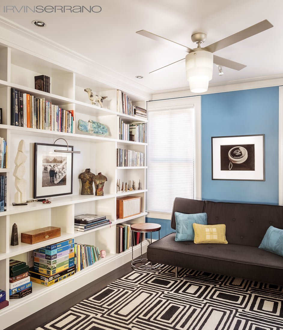 A library featuring a Benjamin Moore Florentine Blue accent wall, an Angela Adams carpet and artwork by Diego Ortiz Mugica.